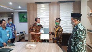Pjs Bupati Rembang, Imam Maskur menyerahkan sertifikat dan kartu BPJS Ketenagakerjaan kepada seorang guru Madin, Rabu sore (14/10).