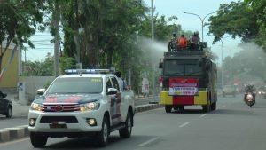 Mobil water canon menyemprotkan disinfektan di sepanjang Jl. Pemuda Rembang. (Foto atas) PJS Bupati dan Kapolres Rembang bersiap-siap menuangkan cairan disinfektan dari atas mobil water canon, Minggu (04/10).