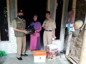 Kasi kedaruratan BPBD Kab. Rembang, Pramujo menyerahkan bantuan kepada korban longsor di Desa Candimulyo, Kecamatan Sedan. (Foto atas) Tebing sungai longsor di Desa Sedan, Kecamatan Sedan.