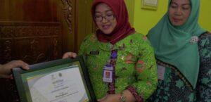 Kepala Dinas Sosial Pemberdayaan Perempuan Dan Keluarga Berencana Kabupaten Rembang, Sri Wahyuni (baju hijau) menunjukkan piagam penghargaan penerima PKH mundur tertinggi se Jawa Tengah. Foto diambil sebelum pandemi Covid-19.