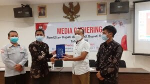 Ketua KPU Kabupaten Rembang, M. Ika Iqbal Fahmi (batik hitam) menyerahkan cindera mata kepada Ketua PWI Kabupaten Rembang, Musyafa Musa di sela-sela kegiatan Media Gathering, Senin malam.