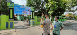 Guru SD N 6 Kutoharjo, Rembang memasang banner pengumuman PPDB di pintu gerbang sekolah, Kamis (29/04).