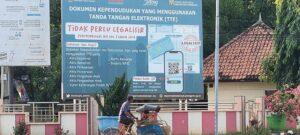 Seorang tukang becak melintas di depan baliho besar di pinggir jalur Pantura Rembang, yang mengumumkan dokumen kependudukan tidak perlu dilegalisir.